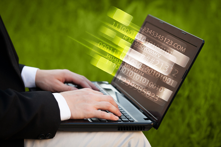input device: Close up of man typing on laptop computer with glowing technology effect Stock Photo