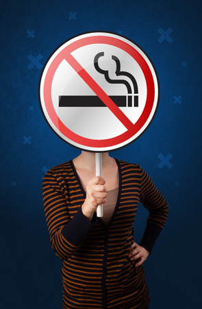 smoking woman: Casual young woman holding round sign with no smoking graphic Stock Photo