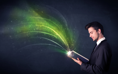 man holding book: Casual young man holding book with green wave flying out of it