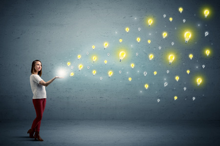 Caucasian woman holding lightbulbs, which are floating away from her hands Stock Photo