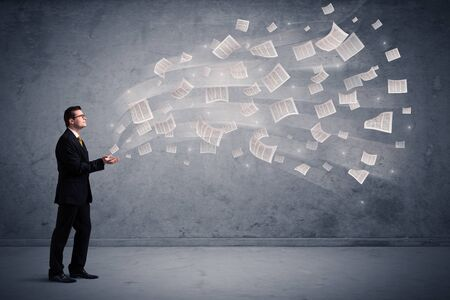 paper sheets: Caucasian businessman holding newspapers, which are floating away from his hands