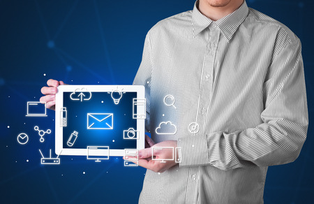 multimedia icons: Casual businessman holding tablet with multimedia icons Stock Photo
