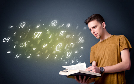 man holding book: Casual young man holding book with shiny letters flying out of it