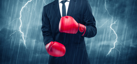 A dangerous sales person getting ready for a fight concept with red boxing gloves and thunder lightning in background. Stock Photo