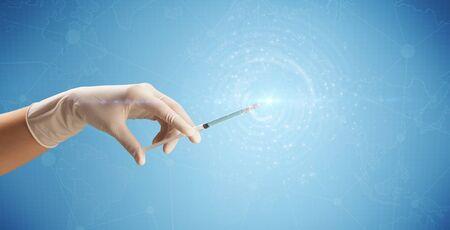Female doctor hand holding syringe with blue background and shine Stock Photo