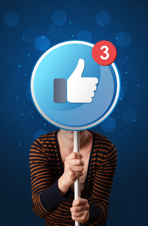 Casual young woman holding round sign with facebook like 報道画像