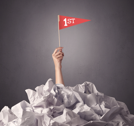 scrunch: Female hand emerging from crumpled paper pile holding a red flag with first written on it
