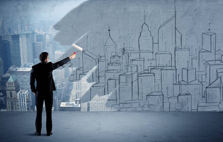 A businessman in elegant suit holding a paint roller in his hand and painting drawn city landscape over urban skyscrapers concept