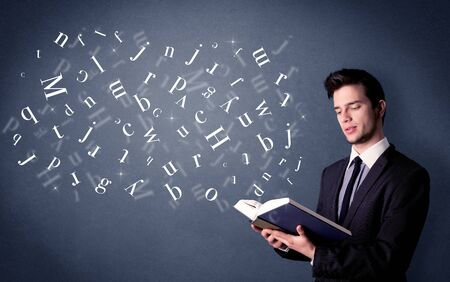 man holding book: Casual young man holding book with white letters flying out of it