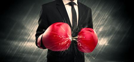 Un hombre de negocios elegante vestido con traje de chocar los guantes de boxeo en su mano con el concepto de la chispa.