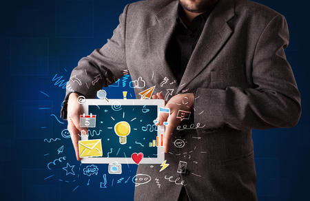 Casual businessman holding tablet with colorful apps