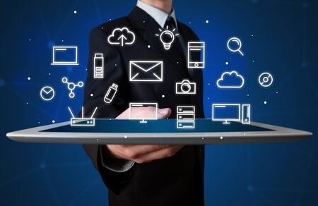multimedia icons: Businessman holding tablet with multimedia icons