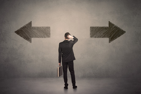 considerations: Business man taking a decision while standing in front of two grungy arrows on wall concept