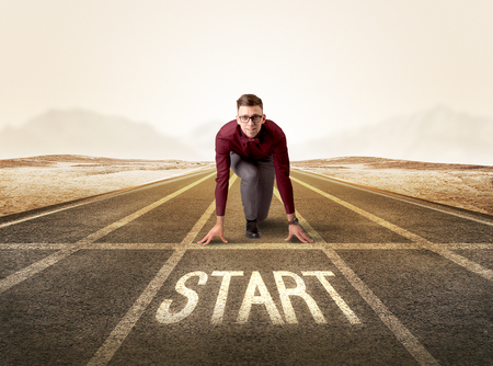start line: Young determined businessman kneeling before start line