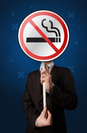 warned: Smart businessman holding round sign with no smoking graphic