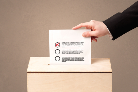 mail slot: Close up of male hand putting vote into a ballot box, on grungy background