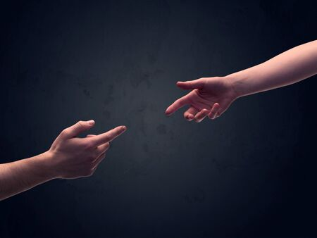 trust god: Two male hands reaching out to one another, almost touching, in front of dark clear empty background wall concept