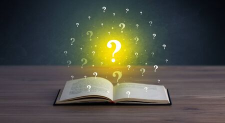 hovering: Yellow question marks hovering over open book Stock Photo