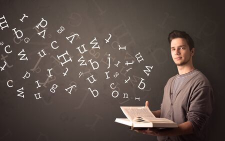 man holding book: Casual young man holding book with white alphabet flying out of it