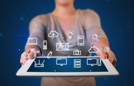 multimedia icons: Casual young woman holding tablet with multimedia icons Stock Photo