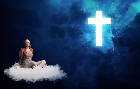 agnosticism: Caucasian woman sitting on a white fluffy cloud looking at a big, bright; blue; glowing cross