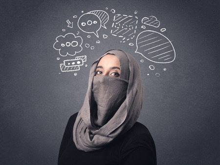 niqab: Young muslim woman wearing niqab with drawn speech bubbles above her head Stock Photo