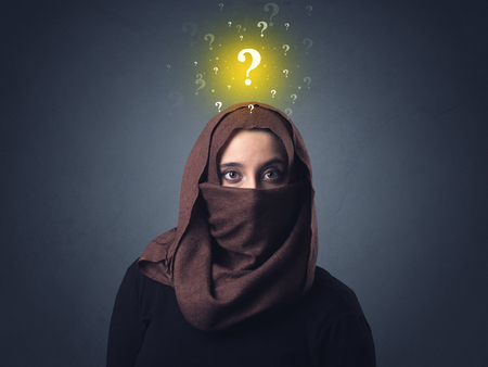 niqab: Young muslim woman wearing niqab with yellow question marks above her head Stock Photo
