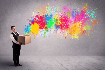 paperboard: A young smiling business male holding a paperboard box with illustration of colourful spray paint splash on urban wall background concept.