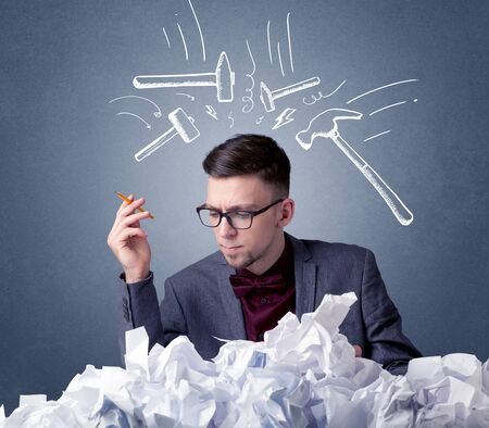 preference: Young businessman sitting behind crumpled paper with drawn hammers hitting his head