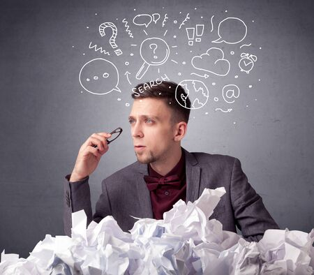 determine: Young businessman sitting behind crumpled paper with mixed doodles over his head Stock Photo