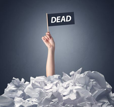 decease: Female hand emerging from crumpled paper pile holding a black flag with dead written on it Stock Photo
