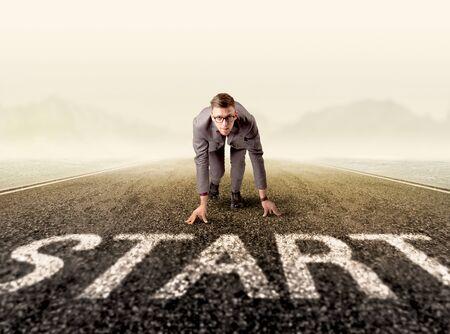 start line: Young determined businessman kneeling at a start line