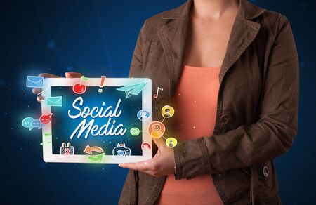 woman tablet: Casual young woman holding tablet with social media icons
