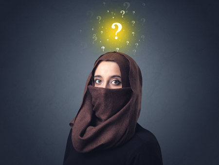 modesty: Young muslim woman wearing niqab with yellow question marks above her head Stock Photo