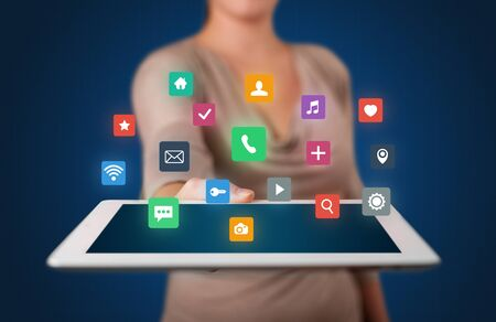 woman tablet: Casual young woman holding tablet with colorful applications Stock Photo