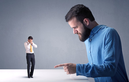 desprecio: Young professional businessman being angry with an other miniature businessman