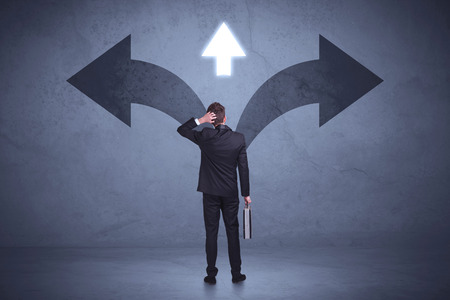 considerations: Businessman taking a decision while looking at arrows on the wall concept background Stock Photo