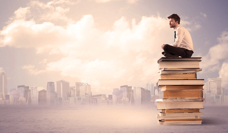 diligent: A serious businessman in elegant suit sitting on a stack of books in front of city scape and clouds Stock Photo