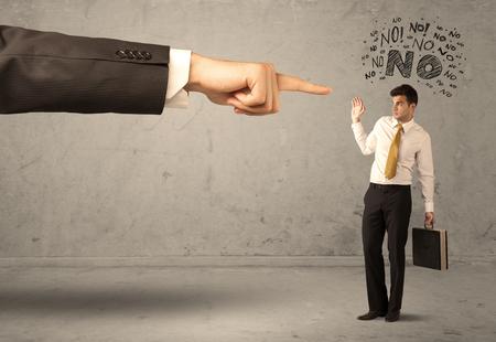 avergonzado: Un joven empleado discrepar y discutir con el jefe, sintiendo concepto avergonzado. Una gran mano apuntando al empresario decir no