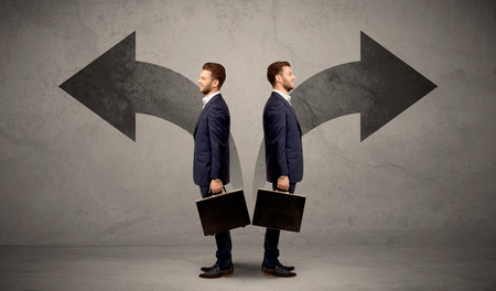 lost in thought: Young conflicted businessman choosing between two directions represented by black arrows