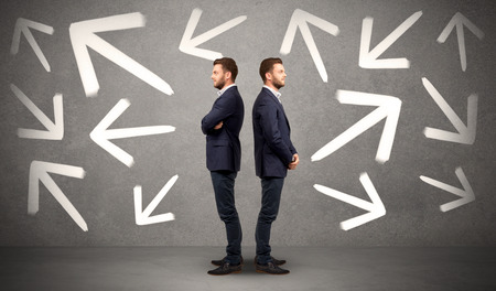 conflicted: Young conflicted businessman choosing between two directions with arrows around him