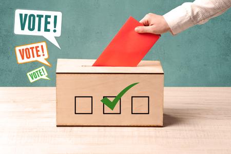 A hand placing a voting slip into a ballot box Stock Photo