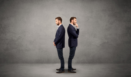 conflicted: Young conflicted businessman choosing between two directions Stock Photo