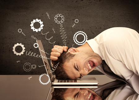 fed up: Falling apart illustration concept with cranks, cog wheels springing from a fed up and tired businessmans head resting on laptop keyboard Stock Photo