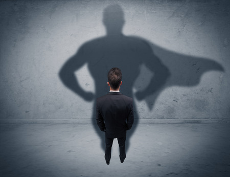 shadow man: A confident young elegant salesman with briefcase facing a wall, looking at his superman shadow concept Stock Photo