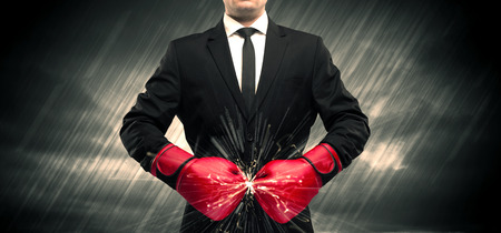 An elegant businessman dressed in suit clashing the boxing gloves on his hand with sparkle concept. Stock Photo