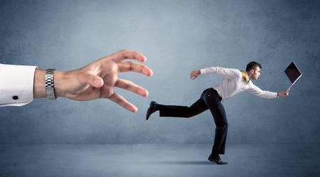Young miniature businessman running from a big hand
