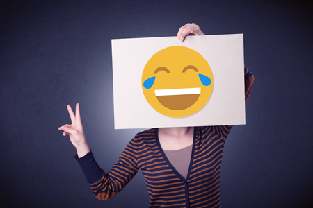 gesticulation: Young casual woman hiding behind a laughing emoticon on cardboard