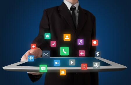 industry electronic: Businessman holding tablet with colorful applications Stock Photo