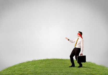 disoriented: Young blindfolded businessman steps on a patch of grass Stock Photo